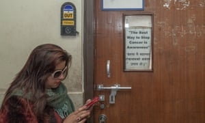 A woman stands by a closed door with a banner creating awareness about cancer
