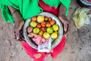 A woman holds a dish of food supplies at her makeshift home in the Xidig IDP camp in Mogadishu.