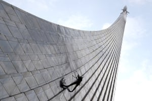 Moscow, Russia. An industrial climber uses a pressure washer to clean the Monument to the Conquerors of Space in the Cosmonauts Alley at the VDNKh exhibition centre