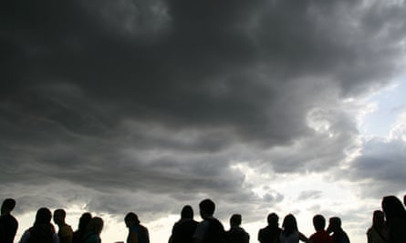 People silhouetted against a dark sky