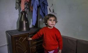 A Syrian refugee child tries to get warm in a slum in the Turkish capital, Ankara