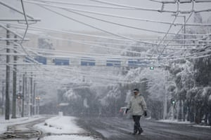 A man walks during heavy snowfall in Athens