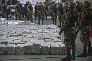 Police officers guard seven tons of seized cocaine in Lima, Peru. The drugs originated in Mexico and were bound for Europe.