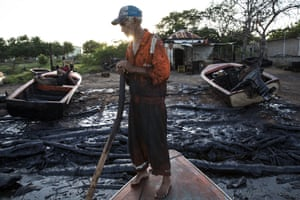 Fisherman William Vilchez stands on his boat on the oil-covered shoreline of Lake Maracaibo