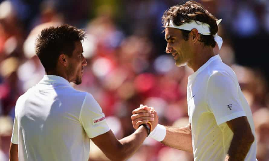 Roger Federer (R) shakes hands with Damir Dzumhur after winning his first singles match.