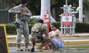 Security forces attend to an unidentified man outside Joint Base Pearl Harbor-Hickam on Wednesday after the shooting.