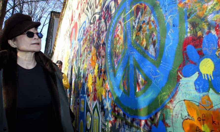 Yoko Ono, John Lennon's widow, stands by the Lennon wall.