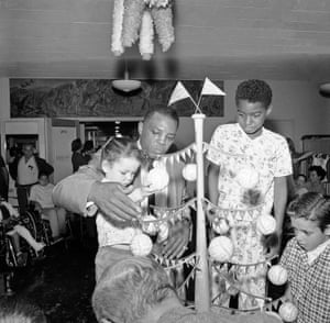 Willie Mays, the San Francisco Giants centrefielder, shows his baseball Christmas tree to two-year-old Lorie Anne, a patient at the Children's Hospital of the East Bay in Oakland, California. The tree, with 20 autographed balls representing every National and American League team, was among 200 unusual Christmas trees donated to the hospital