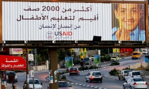 Smiling Palestinian child on a billboard above a road