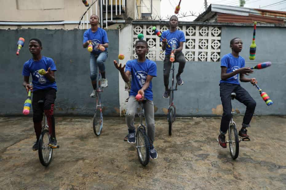 Members of the GKB academy, a unicycle club, juggle during a training session in Lagos, Nigeria, 11 October