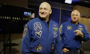 Nasa astronaut Scott Kelly, left, and his twin Mark get together before a press conference on Friday in Houston after Scott's 340-day mission to the International Space Station.