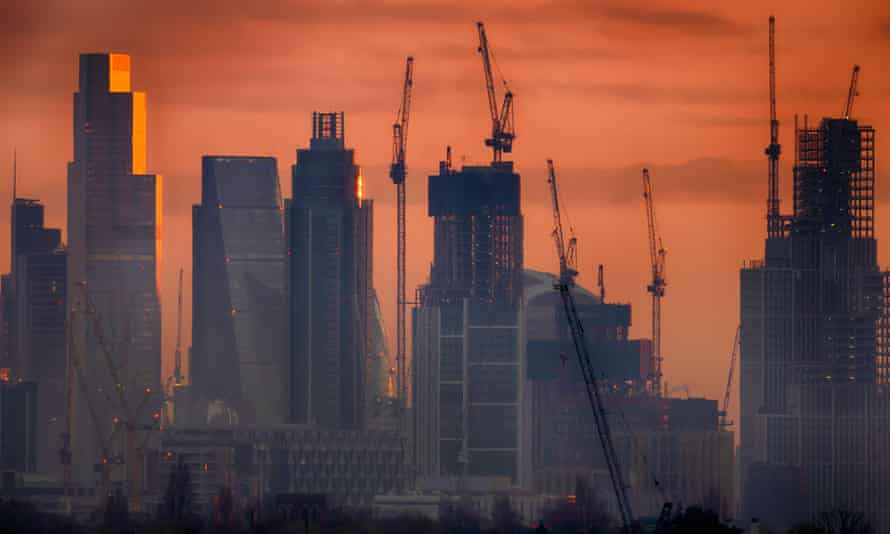 Skyline of City of London skyscrapers at daybreak, with an orange dawn glow behind them