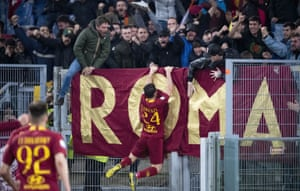 Roma's Alessandro Florenzi clambers up into the stands to celebrate with fans.