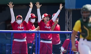 Japanese players celebrate a run score by Minori Naito during the softball game between Japan and Australia.