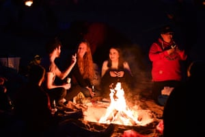 Students from St Andrews University gather round a fire