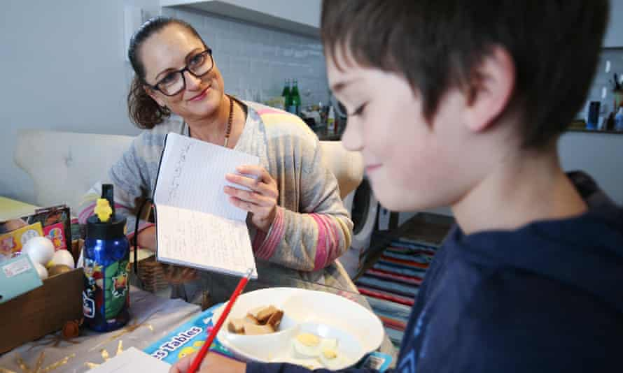 Donna Eddy helps son Phoenix at their home in Sydney. Supporting wellbeing also means accepting neither adult or child might complete a full day's workload, says Pasi Sahlberg.