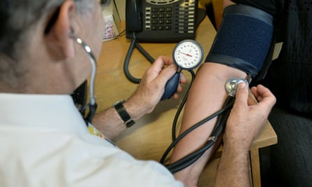 A GP checks blood pressure.