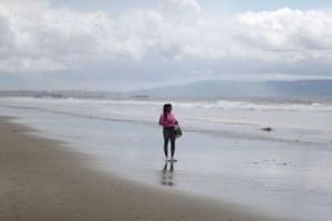 A woman walks along the otherwise deserted beach in Santa Monica, California, U.S.