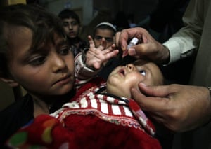 A health worker gives a vaccination to a child in Peshawar, Pakistan