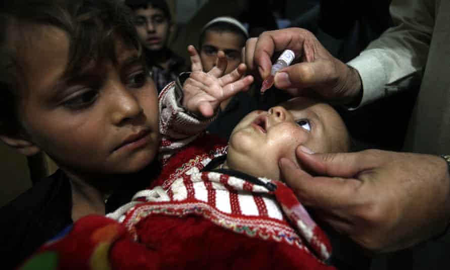 A Pakistani health worker gives a vaccination to a child in Peshawar.
