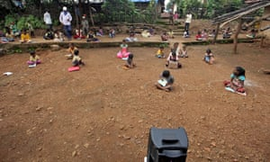 Schoolchildren take pre-recorded lessons sitting in chalk circles on the ground in Dandwal village, Maharashtra state, India.