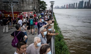 Residents watch the swollen Yangtze River in Wuhan, in China's central Hubei province, on 12 July.