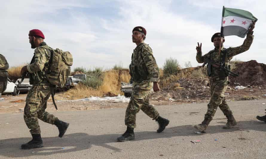 Fighters of the Turkey-backed Free Syrian Army enter Turkey from Syria to fight alongside Turkish forces on 11 October.