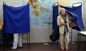 A woman leaves a voting booth at a polling station in Athens.