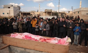 Mourners pray over the coffin of man, killed after an attack hit the village of Kafr Taal, near Aleppo in Syria.