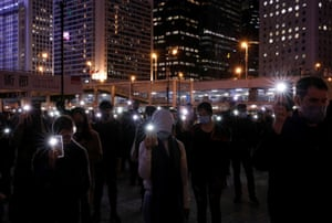 Anti-government demonstrators use the flashlights of their mobile phones at a rally in Hong Kong.