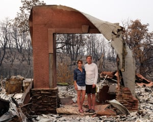 Dawn and Patrick Fowler stand in the ruins of their home in Redding.