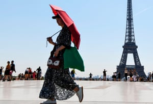 Paris, FranceA tourist uses an umbrella to shelter from the sun as she walks at Esplanade du Trocadero in front of The Eiffel Tower.