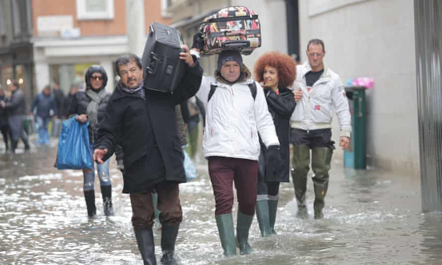 People wade through floodwater in Venice