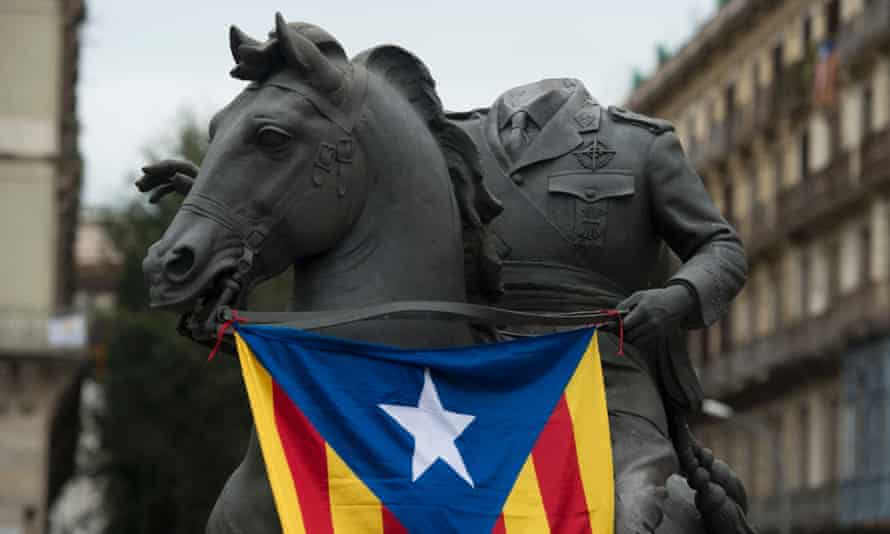 A beheaded sculpture of Francisco Franco riding a horse is draped with a Catalan independence flag in Barcelona.