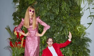 Charlotte, in a sparkling pink dress and pink sunglasses, and Philip Colbert, in a red jacket pretending to skid, in front of their living green wall.