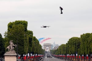 Franky Zapata flies a jet-powered hover board as the  French elite acrobatic flying team flies over the Arc de Triomphe during the Bastille day military parade down the Champs-Élysées.