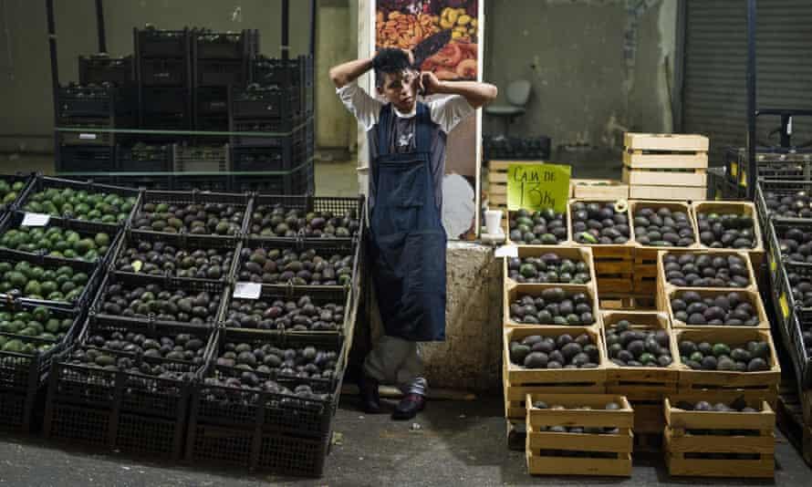An avocado vendor talks on the phone in Mexico City.