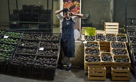 An avocado vendor talks on the phone in Mexico City.