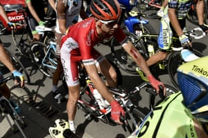 France's Nicolas Edet, injured, waits with others cyclists as the race is neutralised