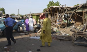 People gather at the site of a suicide bomb attack which took place on 22 June at a market in Maiduguri, Nigeria.