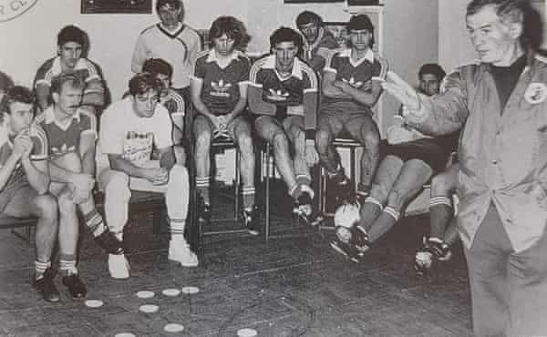 Wade (middle with long hair) clasps his hands in concentration as Socceroos coach Arok teaches tactics with coasters.