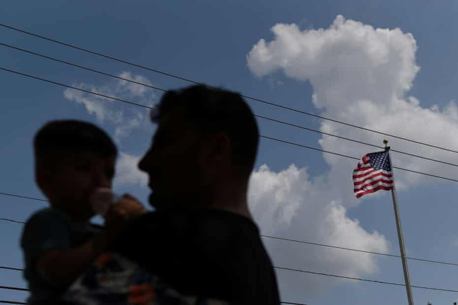 A man and boy are silhouetted against the sky with the US flag in the background.