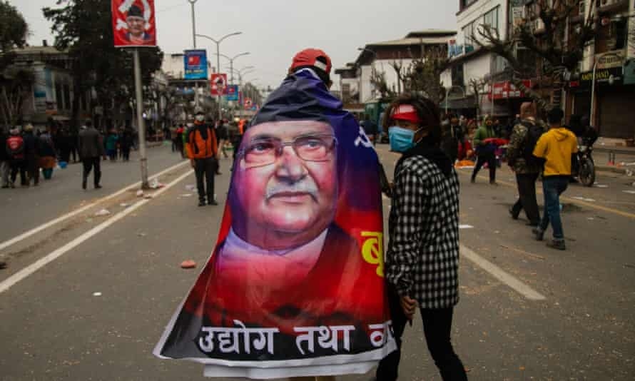 A pro-government activist wrapped in a banner with a portrait of Khadga Prasad Oli.