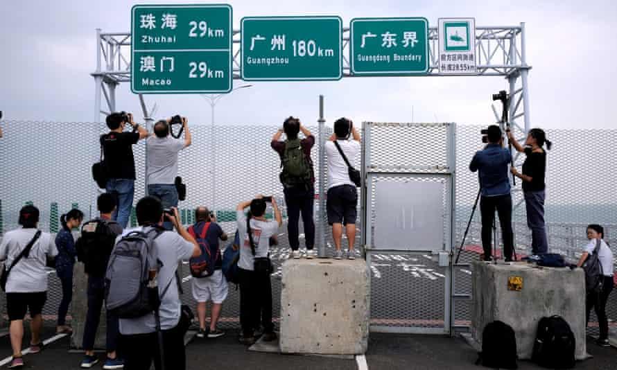 Members of the media take pictures of the Hong Kong-Zhuhai-Macau bridge