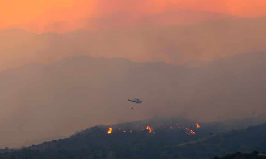 A helicopter flies over the forest fire in Cyprus