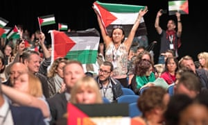 Delegates wave Palestinian flags in response to Colin Monehen's speech