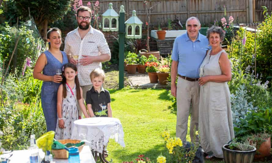 A young family stands apart from a pair of grandparents in a sunny garden.