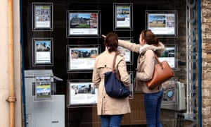 People looking at an estate agent's window