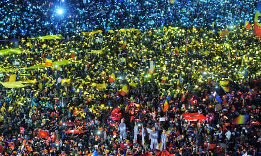 Thousands of protesters in Bucharest create a huge flag using coloured paper in blue, yellow and red lit by their mobile phones