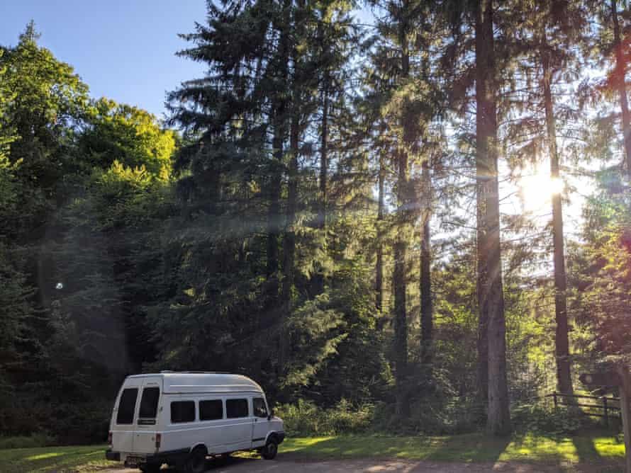 A van in woods.